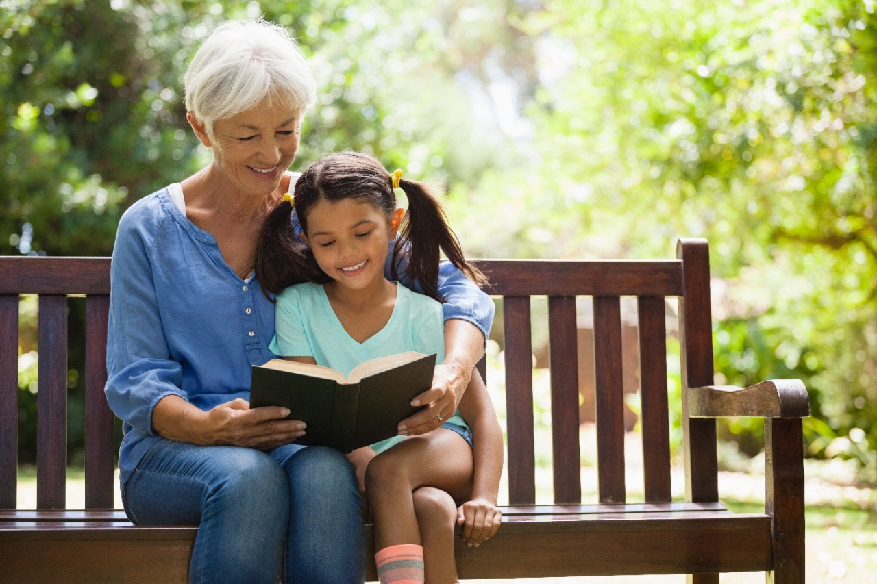 Smiling grandmother reading novel to granddaughter sitting on wooden bench at garden