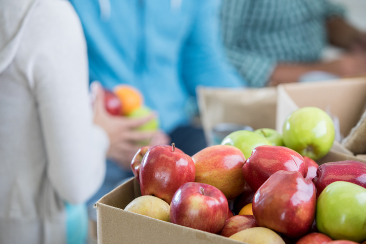 Close up of a box of red and green apples. People are in the background organizing the food that has been donated to a food bank.