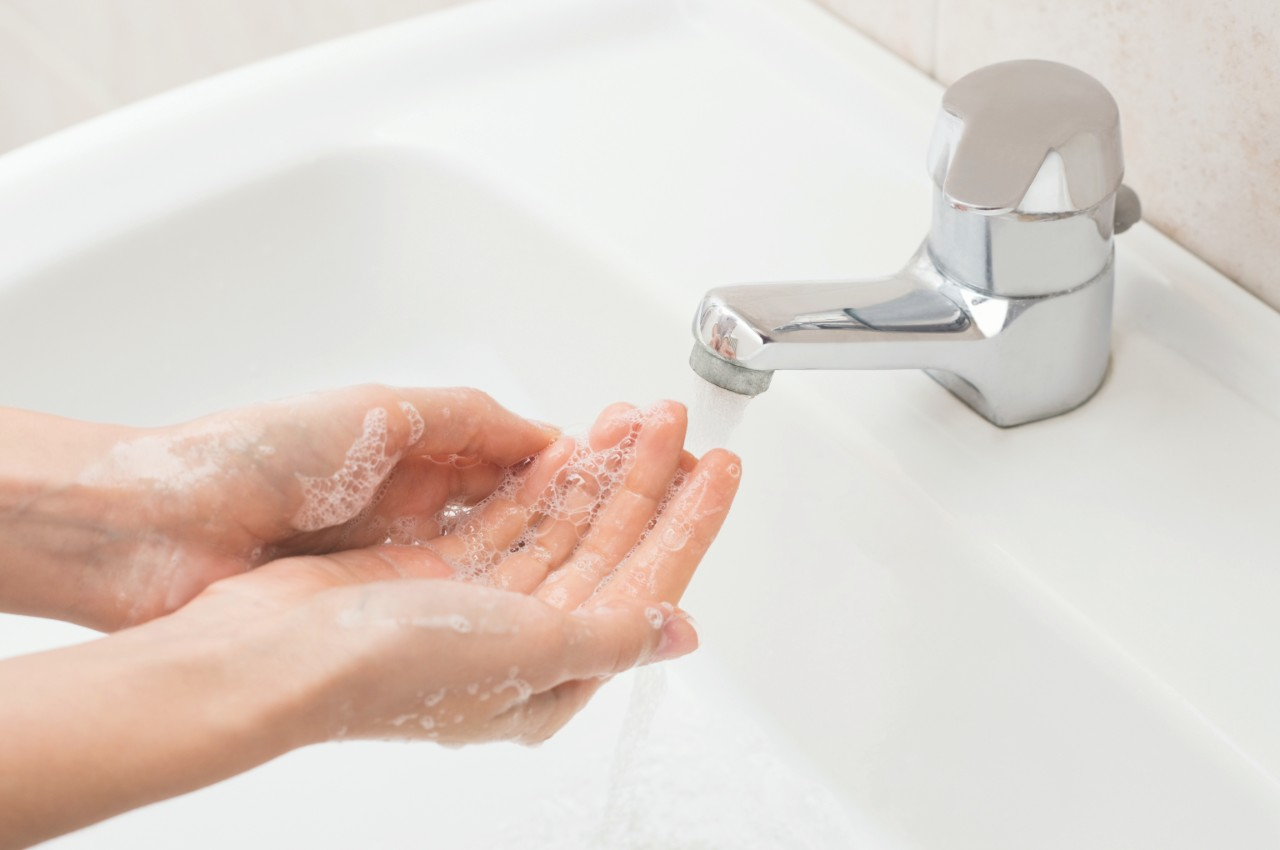 Closeup shot of a woman washing hands with soap lather over bathroom sink. Girl cleaning hand.